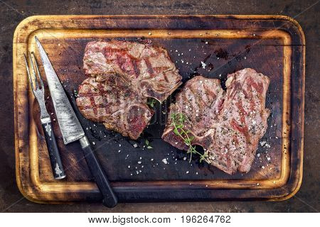 Two Barbecue dry aged Wagyu Porterhouse Steaks as close-up on a cutting board