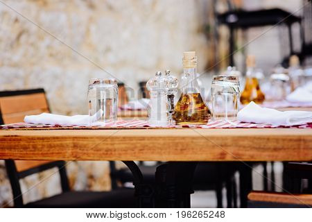 Outdoor restaurant table with olive bottle and spices