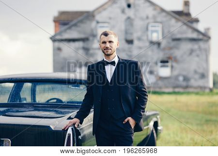 Confident wealthy young man in suit near classic car