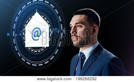 business, people and future technology concept - businessman with e-mail message hologram over black background