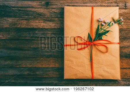 gift wrapping paper tied with a red ribbon and a Daisy flower on wooden retro grunge background with space for text top view close up tinted photo