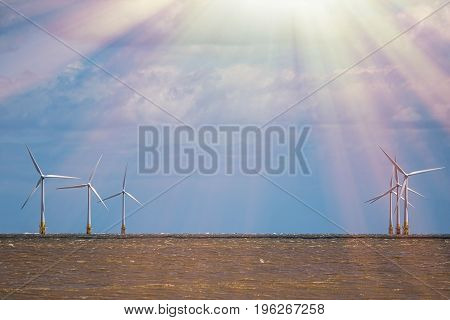 Natural sustainable resources. Bright future of renewable energy production. Offshore windfarm on sea horizon with beaming sunlight. Beautiful seascape with copy space.