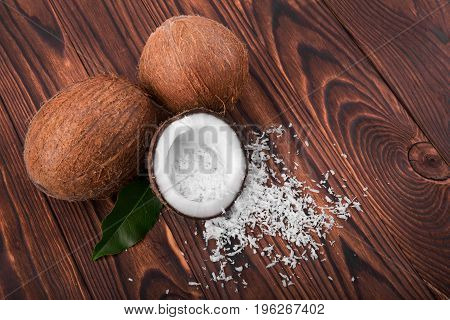 A group of nutritious coconuts on a dark wooden background. A view from above on exotic brown coconuts with coco chips, close-up. Beautiful ingredients for summer desserts.
