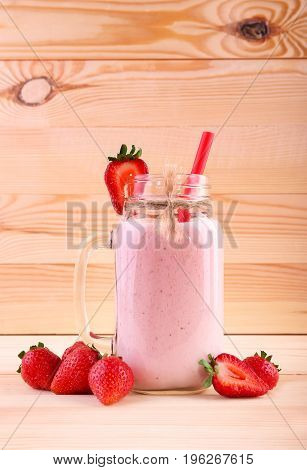 A close-up of a tall mason jar filled with a creamy pink cocktail on a light brown wooden background. Blended smoothie with a cut red berry on the top and raw ripe strawberries.