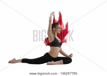 Young sexy fitness model in sports top and leggings sitting in split holding red cloth isolated studio shot