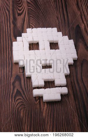 A terrifying skull symbol made of sugar cubes laying on a dark brown wooden background. Granulated pieces of sugar forming a death sign. Deadly sugar addiction concept.