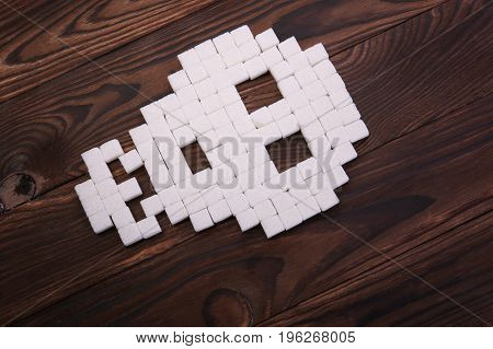 Granulated sugar lying in a picture of a skull on a dark wooden background. White sugar cubes on a brown table. Disastrous effects of a sugar addiction. Crystalline sweetener.