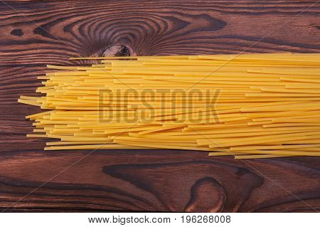 Tasteful pasta noodles on a dark brown wooden background. Long bright yellow spaghetti for delicious homemade meals. Wheaty organic ingredients for italian restaurants.