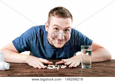 A cheerful guy with medicaments isolated over the white background. A healthy student in a cotton t-shirt with pills and a glass of fresh water. Successful medical treatment concept.