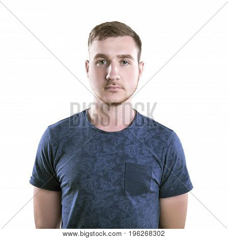 A modern young man standing in a dark blue t-shirt isolated over the white background. A serious and confident male with light brown hair. An attractive guy with a neutral expression.