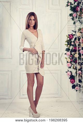 Beautiful Romantic Woman Posing In Fashion Elegant White Dress And High Heels On Light Wall Backgrou