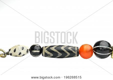 Beautiful variety of ancient etched agate separated with orange round shaped of carnelian in necklace isolated on white background Myanmar