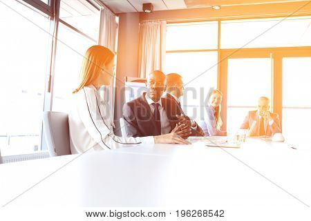 Young businessman talking with female colleague in board room