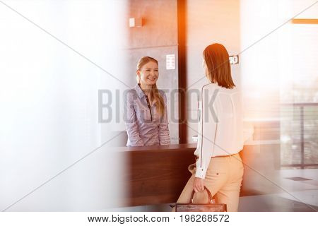 Happy young receptionist talking with businesswoman in office