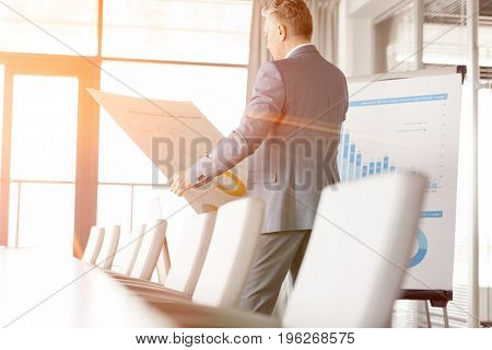 Mature businessman analyzing graph on chart in board room