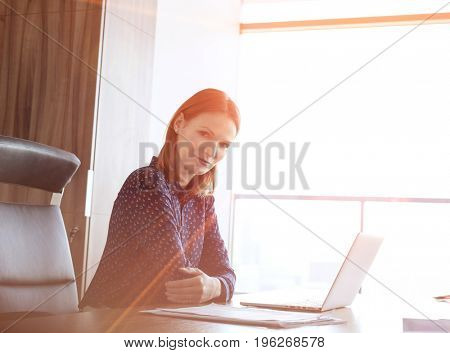 Portrait of confident young businesswoman with laptop at desk in office