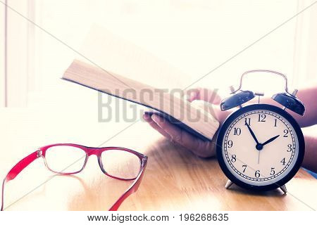 Reading book on table. focus on retro alarm clock. Time to read concept.