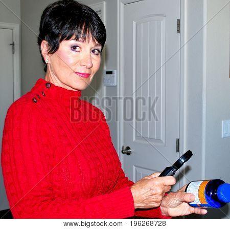 Mature female senior with vitamin pills to take at home.
