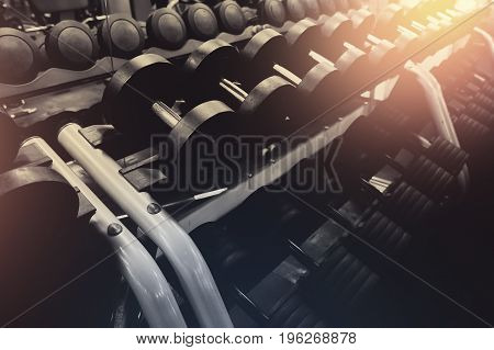 lot of dumbbells stand in row in the gym, glare of light. Concept slimming, musculature, bodybuilding.