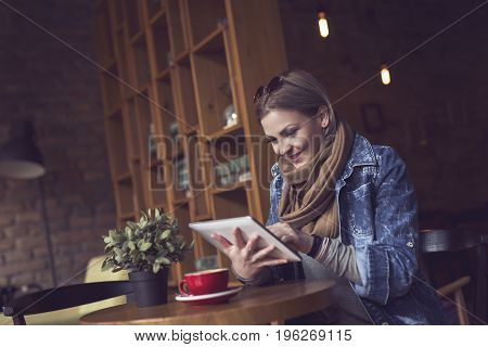 Beautiful young blond sitting in a cafe pensive having a morning coffee holding a tablet computer and surfing the net