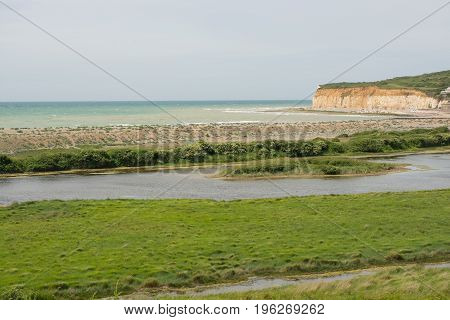 River Cuckmere shingle beach and chalk cliffs at Cuckmere Haven near Eastbourne East Sussex England.