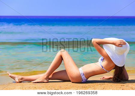 Woman in big straw sunhat sunbathing on a sandy beach. Summer holidays concept