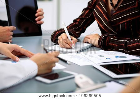 Group of business people at meeting, close up. Boss pointing into tablet computer monitor.
