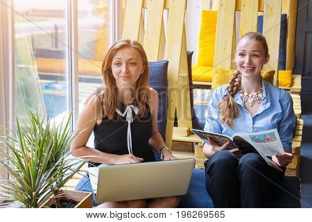 Pretty businesswomen working together with new startup project using laptop computer in modern loft. People and teamwork concept - happy creative team in office. Casually dressed female colleagues talking in a meeting room.
