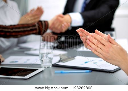 Close up of female applause while business people shaking hands at meeting.