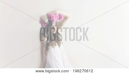 Hipster Woman With Peonies Wreath And In White Dress Posing In White Room. Sensual Boho Bride With P