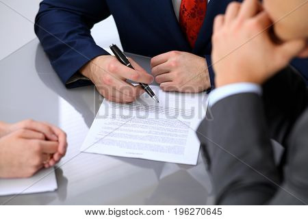 Business man is going to sign contract. Group of business people at meeting.
