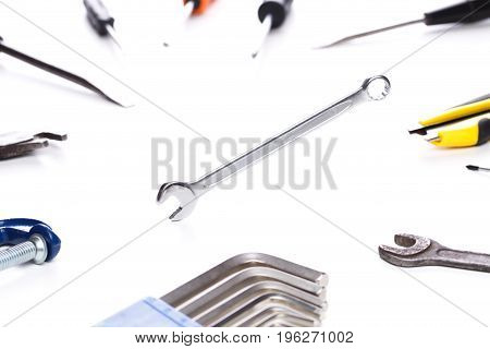 Photo of various tools on clean white background with wrench in the center