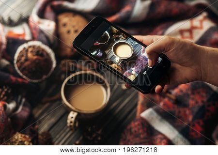 hand holding phone taking photo of stylish winter flat lay coffee cookies and spices on wooden rustic background. cozy mood autumn. instagram blogging workshop concept