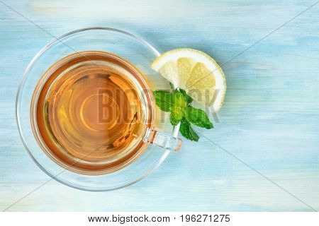 An overhead photo of a cup of vibrant tea with fresh mint leaves and a wedge of lemon, shot from above on a teal blue texture, with a place for text