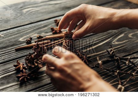 Stylish Rustic Winter Picture With Hands Arranging Anise And Pine Cones On Wooden Background. Space