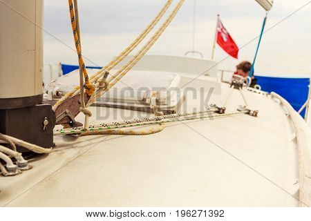 Detailed close up of down side of sail mast on boat during sea cruise. Yachting sailing objects concept.
