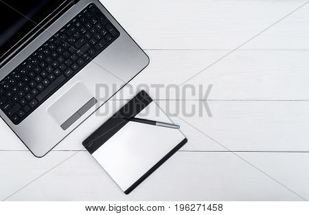 Wooden White Office Desk Table With Open Blank Laptop Computer And Graphic Tablet, Free Space. Top V