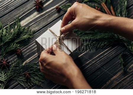 Hands Wrapping Christmas Simple Present Tying Bow On Stylish Rustic Wooden Background With Space For