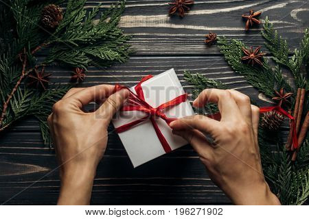Stylish Christmas Flat Lay With Hands Wrapping Present With Red Ribbon On Rustic  Wooden Background