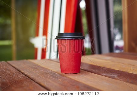 Red paper cup to takeaway on wooden floor outside the cafe. Surfing boards stand behind at the background