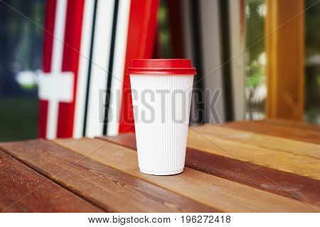Ripple white paper cup to takeaway on wooden floor outside the cafe. Surfing boards stand behind at the background
