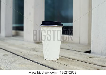 Ripple white paper cup of coffee to takeaway at the wooden floor terrace outside
