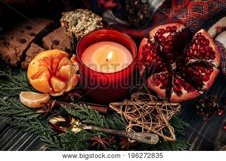 Christmas Candle And Presents With Red Ribbon And Garnet Cookies Fruits On Stylish Rustic  Wooden Ba