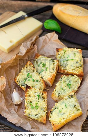 Bread baguette baked with grated cheese garlic and basil leaves