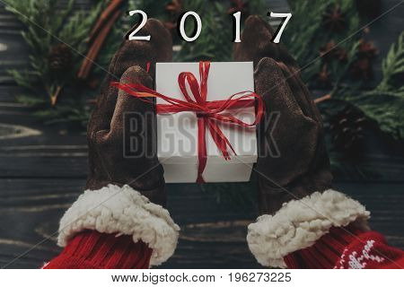 Hands In Stylish Gloves Giving Christmas Present With Red Bow Flat Lay On Rustic Wooden Background W