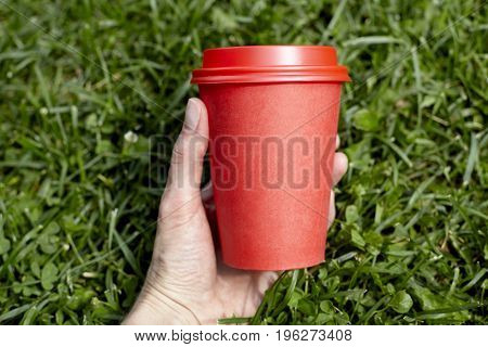 Red paper cup of coffee to takeaway on green grass lawn in woman hand. Breakfast morning outside the cafe
