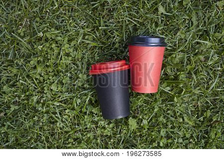Two paper cups with coffee to take away red and black cup on green grass outdoor breakfast