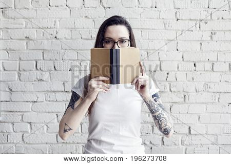 Pretty hipster tattooed woman poses in white t-shirt with book in hands isolated on white brick wall Hold a book in hand space for design layout