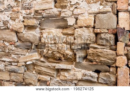 The background of the large natural stone textured wall with cracks close up . A horizontal frame.