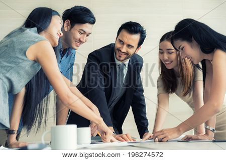 Group of multi-ethnic business partners discussing ideas in meeting room at office. Business people meeting corporate communication teamwork concept.